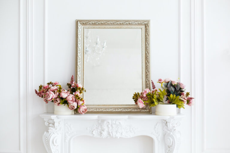 luxurious and expensive looking mirror with gold framing, resting onto of a white fireplace mantle decorated with flower pots on either side